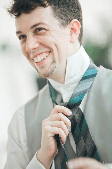 groom getting ready tie the  tie