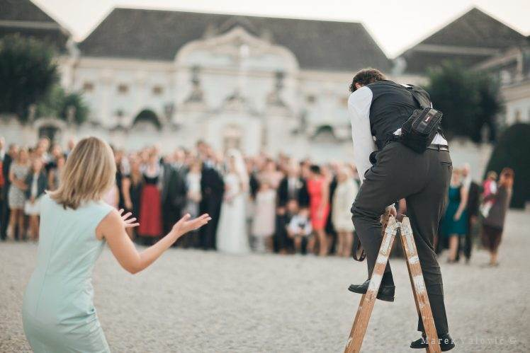 profesional wedding photographer on a ladder taking photos - Schloss Halbturn