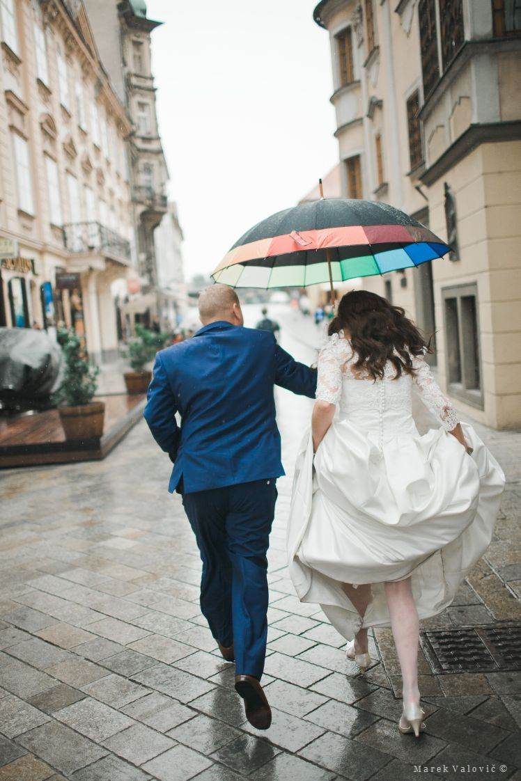 running in rainy wedding day with umbrella
