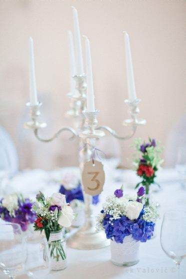 candle and blue and purple wedding decoration on table
