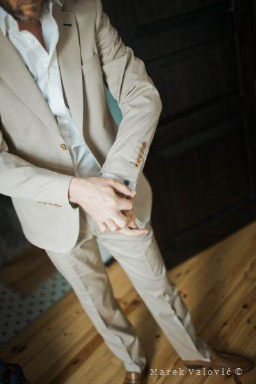 groom fetting ready - wearing creamy suit